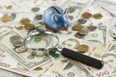 Oekraïense hryvnia en de Amerikaanse dollars van ` s met een spaarvarken en een vergrootglas Stock Afbeelding