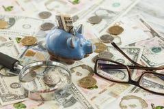 Oekraïense hryvnia en de Amerikaanse dollars van ` s met een spaarvarken en een vergrootglas Royalty-vrije Stock Afbeeldingen