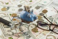 Oekraïense hryvnia en de Amerikaanse dollars van ` s met een spaarvarken en een vergrootglas Royalty-vrije Stock Afbeelding
