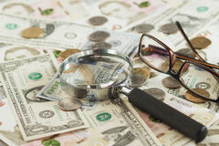 Oekraïense hryvnia en de Amerikaanse dollars van ` s met een vergrootglas Royalty-vrije Stock Foto's