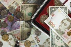 Oekraïense hryvnia en de Amerikaanse dollars van ` s met vergrootglas Royalty-vrije Stock Afbeeldingen