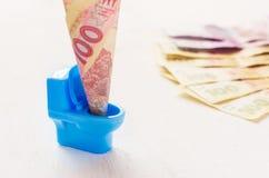 Oekraïense hryvnia honderd in een blauw stuk speelgoed toilet Royalty-vrije Stock Afbeeldingen