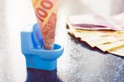 Oekraïense hryvnia honderd in een blauw stuk speelgoed toilet Stock Foto