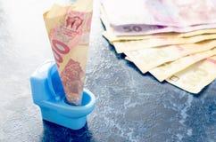 Oekraïense hryvnia honderd in een blauw stuk speelgoed toilet Royalty-vrije Stock Fotografie