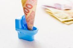 Oekraïense hryvnia honderd in een blauw stuk speelgoed toilet Royalty-vrije Stock Afbeelding