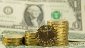 Oekraïense munthryvnia (grivna) op de achtergrond van de rekeningen van de 1 dollar V.S. (1 USD) Royalty-vrije Stock Foto's