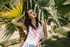 Oemotståndlig flicka med mörkt rakt hår som vilar i skugga av palmträd som tycker om semester i exotiskt land St?ende royaltyfri bild