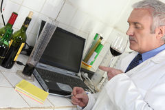 Oenologist analysing a wine. And recording results stock photos