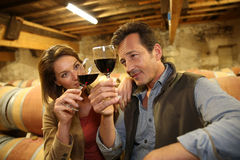 Oenologists in wine cellar with a glass of wine. Oenologists in wine cellar tasting red wine Royalty Free Stock Photos
