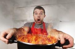 Oerfaren hem- kock med bränning för förklädeinnehavkruka i flammor med uttryck för spänningsnödframsida arkivfoton