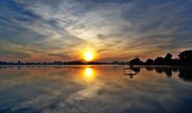 Oerhörd lek av ljus i himlen och vattnet på soluppgång över sjön arkivbild