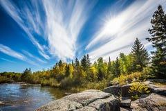 Oerhörda cirrusmolnmoln och enorma plana stenar i den gamla Pinawa fördämningen parkerar Indiansommar i Manitoba, Kanada Begreppe royaltyfri fotografi