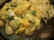 Oesters met eieren op de hete pan worden gebraden die Stock Afbeelding