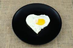 Oeuf au plat dans la forme du coeur du plat noir Photographie stock