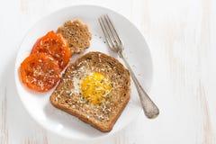 Oeuf au plat dans un pain grillé et des tomates grillées pour le petit déjeuner Image stock