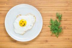Oeuf au plat de sourire se trouvant d'un plat blanc sur une planche à découper en bois avec le groupe d'aneth Concept classique d Photographie stock libre de droits