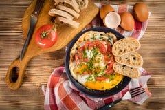 Oeuf au plat fait maison de petit déjeuner avec la tomate Photos stock