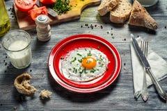 Oeuf au plat pour le petit déjeuner avec du pain et des légumes Images libres de droits