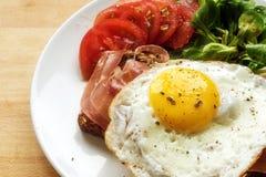 Oeuf au plat sur le pain avec du jambon garni avec de la salade verte et le tomat Images stock