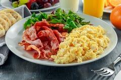 Oeuf brouillé de matin, petit déjeuner de lard avec le jus d'orange, lait, fruit, pain du plat blanc Photographie stock