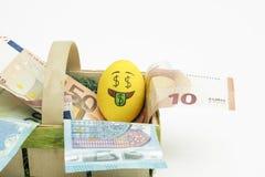 Oeuf d'Emoji pâques avec des fonds d'amour de l'expression du visage I placés sur l'euro monnaie fiduciaire Photographie stock