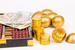 Oeuf d'or, pièce d'or et dollar sur le fond blanc Photos libres de droits