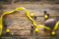 Oeuf de chocolat de Pâques, dragées de sucrerie, ruban en soie jaune Photos libres de droits