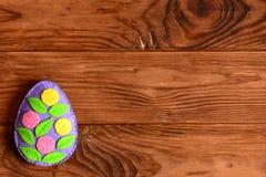 Oeuf de feuille et de fleur fait à partir du feutre Oeuf de pâques lumineux de feutre sur le fond en bois brun avec l'endroit vid Images stock