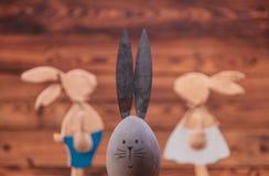 Oeuf de pâques avec des oreilles de lapin devant des couples de lapins Photographie stock