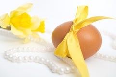 Oeuf de pâques avec le ruban jaune sur le fond blanc image libre de droits