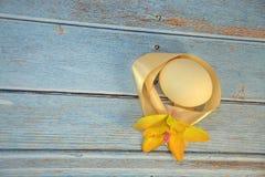 Oeuf de pâques avec un ruban jaune de satin et un bourgeon d'une orchidée sur une table en bois images libres de droits