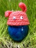 Oeuf de pâques bleu avec le chapeau rose avec des yeux sur l'herbe verte Images libres de droits