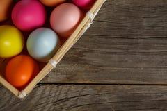 Oeuf de pâques coloré dans le nid sur le fond en bois avec l'espace photographie stock
