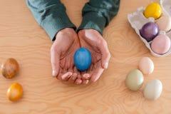 Oeuf de pâques dans des mains tendues ; oeuf de pâques pour vous photo libre de droits