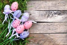 Oeuf de pâques en plastique rose et pourpre sur l'herbe Image stock