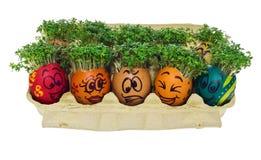 Oeuf de pâques peint dans un visage souriant drôle et des modèles colorés Photos stock