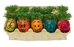 Oeuf de pâques peint dans un visage souriant drôle et des modèles colorés Photos libres de droits