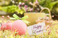 Oeuf de pâques rose dans l'herbe Photographie stock