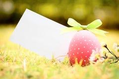 Oeuf de pâques rose dans l'herbe avec l'arc-noeud vert et la salutation vide Photographie stock libre de droits