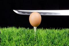 Oeuf de pâques sur le té de golf avec l'épée Image libre de droits