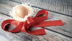Oeuf de poulet dans un nid de paille et de ruban rouge de satin sur une table en bois photographie stock