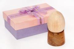 Oeuf en bois de Pâques sur le support en bois avec le beau boîte-cadeau Photographie stock libre de droits