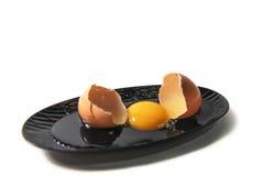 Oeuf et coquille crus d'oeufs de plat noir Photographie stock