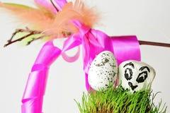 Oeuf et pierre de pâques blancs avec le visage d'oiseau sur la surface herbeuse avec le fouet traditionnel de korbash à l'arrière Photo stock