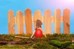 Oeuf rouge peint de Pâques à la barrière en bois sur la mousse verte Photographie stock libre de droits
