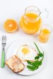 Oeuf sur le plat et une cruche de jus d'orange Photographie stock libre de droits