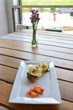 Oeufs, épinards sur le pain Toasted avec la tomate découpée épicée du côté avec la fleur et fenêtre à l'arrière-plan Image libre de droits