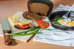 Oeufs au plat avec des herbes et des tomates dans une casserole Photo stock