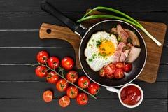 Oeufs au plat avec du jambon dans la casserole sur le fond noir Photo libre de droits