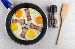 Oeufs au plat avec la poitrine dans la poêle, pot avec le condiment, spatule sur la table Vue sup?rieure photographie stock